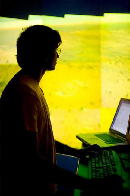 silhouette of young man standing at a computer keyboard